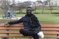 Young Black Man Leaning Back on Park Bench Confidently