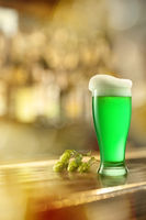 Glass of fresh green beer on a table in a bar.