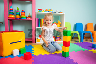 The girl builds a tower of cubes in the playroom