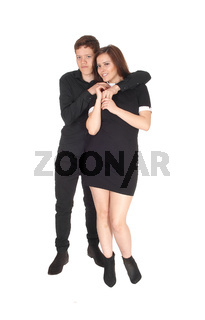 A beautiful young couple standing smiling in the studio