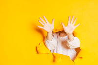 Child hands is showing ten fingers through a ripped hole in yellow paper, with copy space.