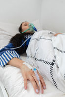 The teenager lies sick connected to a respirator because she has trouble breathing.