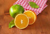 Green grapefruit and halved orange