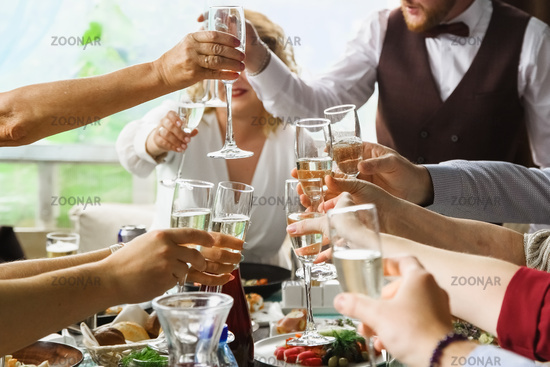 glasses with champagne in hand over the table
