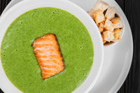 Delicious green spinach cream-soup with salmon
