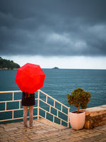 Woman with red umbrella watching storm clouds on the shore of Rovinj