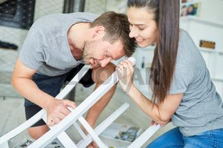 Junges Paar als Heimwerker beim Stuhl aufarbeiten