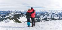 Senior couple is hiking in alpine snow winter mountains enjoying panorama view. Allgau, Bavaria, Germany.