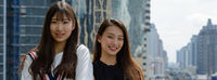 Two happy young beautiful Asian teenage girls smiling together against view of the city