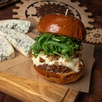 Fresh craft beef burger with fresh arugula salad and, fresh blue cheese slices laying next to it. Restaurant concept. Street food concept