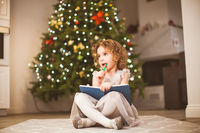Dreamy girl sitting near decorated Christmas tree