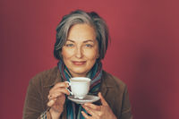 Beautiful caucasian woman holds white cup drinking coffee in studio on pink background. Happy gray-haired female looking at camera. Tinted image