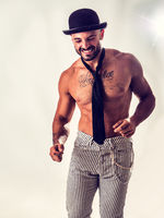 Handsome shirtless muscular man standing with bowler hat and neck-tie on naked torso