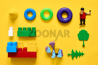Flat lay of plastic and eco wooden toys. Developing games. Yellow background