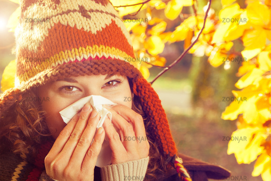 Woman sneezing into a handkerchief surrounded by autumnal yellow and orange leaves. Fall and seasonal diseases concept.