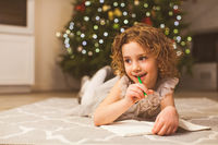 Smiling girl thinking about Christmas wish list
