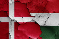 flags of Denmark and Hungary painted on cracked wall