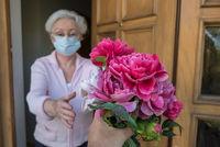 Seniorin mit Munfschutz bekommt Blumen an der Haustür