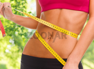 close up of woman measuring her waist with tape