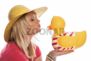 frau mit strohhut küsst eine badeente