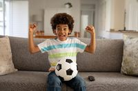 Boy with football cheering while watching sports on TV