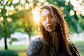 Young beautiful woman outdoors on green background summer nature