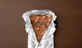milk chocolate bar with nuts in foil wrapper