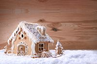 Gingerbread house on white snow isolated on wood