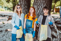 Friends picking up trash from the park. They collecting the litter in garbage bag
