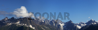 Panorama of high rocky mountains with glacier and sunlit blue sky