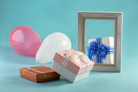 Composition with photo frame, gift boxes and balloons.
