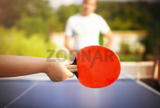 Unrecognizable child plying ping pong with father