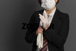 Business Woman in protective mask put on disposable gloves. Close up shot. Focus on female hand in foreground. Pandemic concept