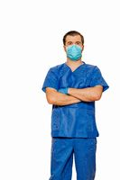 Male doctor in scrubs wearing protective face mask and gloves with cross hands waiting for patients
