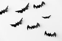 flock of black paper bats over white background