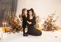 Charming woman and girl in Halloween costumes