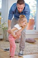 Vater hilft Tochter beim Hose anziehen