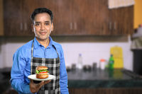 Indian Male Chef with a Burger in a Kitchen