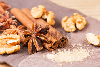 Star anise walnut brown sugar with cinnamon at christmas time on cloth background