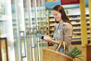 Frau nimmt Tiefkühlkost aus Kühlregal