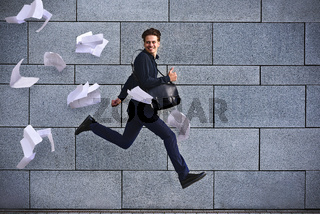 Smiling businessman running fast with briefcase at city