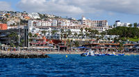 Tenerife, Spain - October 15, 2019: Waterside distant view Los Cristianos coastline, people enjoy warm Atlantic Ocean pretty beach, touristic town, situated on south coast of Canary Islands, Spain
