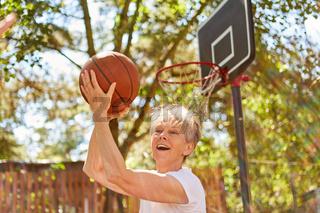 Senior Frau als vitaler Rentner mit Basketball