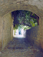 typical quiet cobbled street in rhodes town with an a stone arch and old buildings