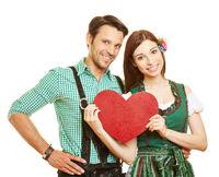 Paar in Tracht hält rotes Herz