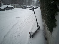 Snow-covered rental e-scooter standing on the side of a sidewalk in winter during heavy snowfall