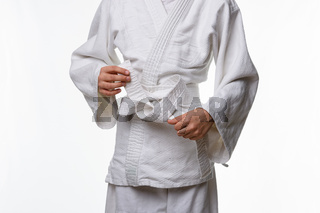 Stages of correct tying of the belt by a teenager on a sports kimono, step eight