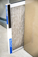 Old dirty furnace filter partially removed from holder