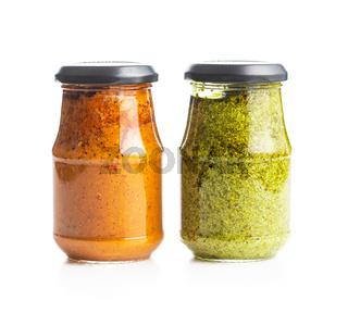 Green basil and red tomato pesto dip sauce in jar.