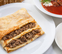 Pancake stuffed with meat and borsch with greenery